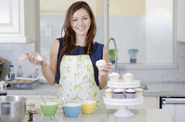 Cute housewife decorating cupcakes