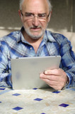 homme senior se servant d'une tablette