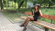 The beautiful sexy girl smokes in park