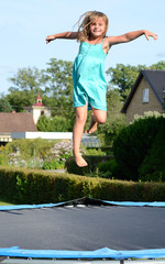 Cute young girl jump on garden trampoline