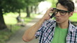 Young man talking on cellphone in the park, steadicam shot