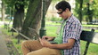 Young happy man with laptop in the park, steadicam shot