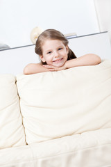 Little girl leans to the white leather sofa