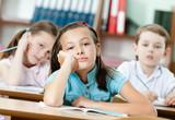 Tired beautiful schoolgirl dreams at the school desk