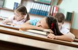 Tired schoolgirl sleeps at the desk