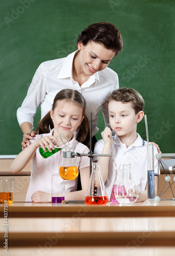 Little pupils study chemical liquids with their teacher