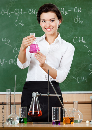 Smiley chemistry teacher holds a conical flask