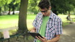 Happy young man with tablet computer in park, steadicam shot