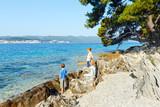 Fototapety Summer stony beach and family on it (Croatia).