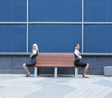 A quarrel between two young businesswoman sitting on a bench