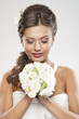A young brunette bride holding a bouquet of white roses