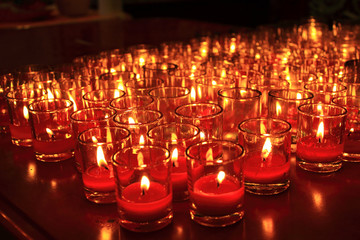 Many red votive candles light the darkness in church
