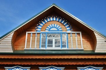 Wooden fretted roof with window on blue sky