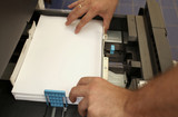 details of hand inserts a paper A4 into a laser copier