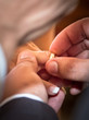 Groom putting wedding ring on bride finger