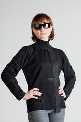 Woman in sunglasses standing with arms akimbo