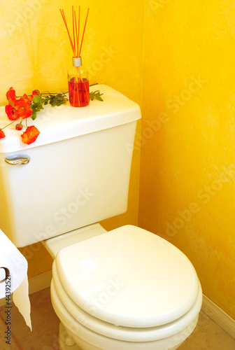 Toilet in Yellow Bathroom with Diffuser and Flowers