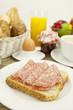 frisches frühstück mit toast, salami, ei und saft auf einem Ti