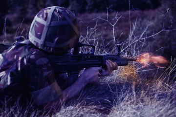 Young soldier with gun shooting in the dark