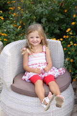 Little girl sitting on a wicker chair