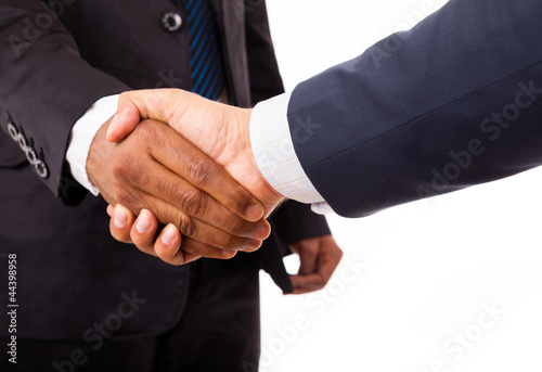 Closeup of an african and caucasian business man handshake - iso