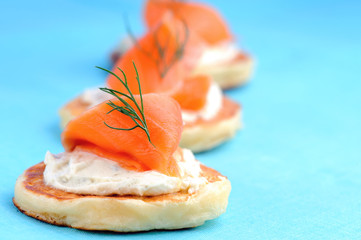Trio of salmon canapes on blue background