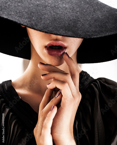 girl in black hat touching face and lips - 44400948