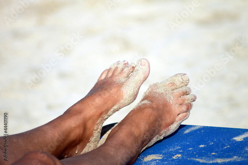 Feet of sunburnt woman on beach