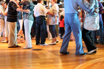 Many happy senior couples in love dancing on wooden dance floor.