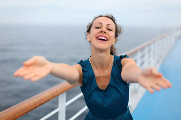 Beautiful woman stands on board of large ship