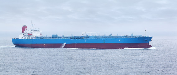 Large cargo ship with red and blue boards floats in open ocean