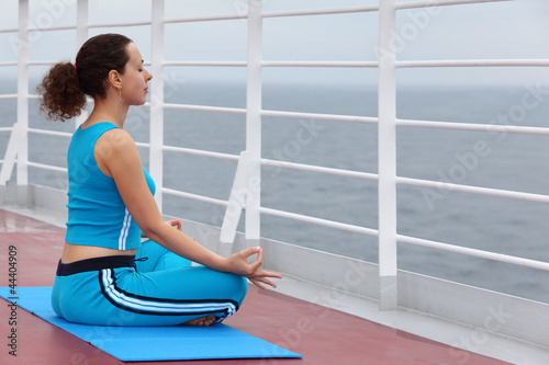 Young woman dressed in blue sports suit sits on cruise liner