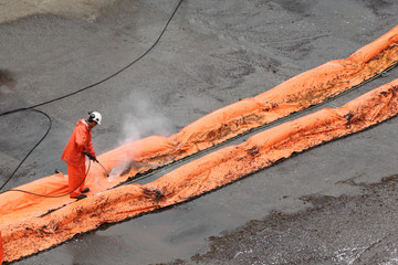 Worker washes orange slick bar by water from hose