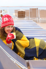 Happy woman wearing in red mittens and plaid lies on lounger