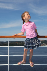 little girl wearing t-shirt stands at railing on deck of ship