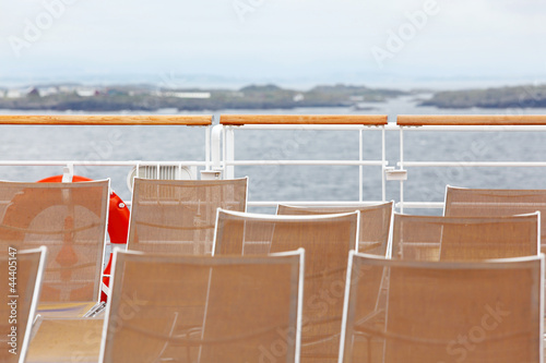 Many sun loungers are on deck of ship.