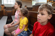 Mother, daughter and son sit on bench in Catholic Church