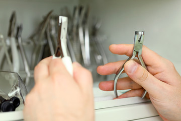 Man hands held metal dental instruments. Focus on right hand.