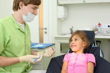 Dentist prepares to treat teeth of girl in dental clinic