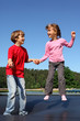 Happy brother and sister jump on trampoline on sunny summer day