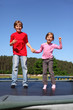 Smiling brother and sister jump on trampoline on sunny day