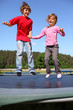 Joyful brother and sister jump on trampoline at sunny summer day