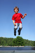 Joyful boy dressed in red T-shirt jumps on trampoline
