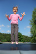 Joyful girl dressed in pink T-shirt jumps on trampoline