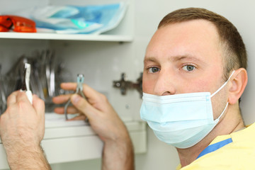 Dentist in mask holds metal dental instruments and looks