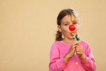 Girl wearing pink blouse with red clown nose sucks candy