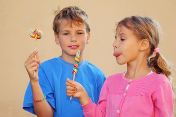 Girl and boy with multicolored candies. Sister looks at candie