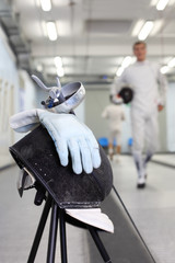 Close up of foil, mask and white glove at background of fencer