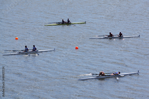Four sports boats with pairs of rowers on water at sunny day.