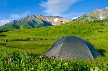 Tourist tent in the in mountains, blue sky and lake